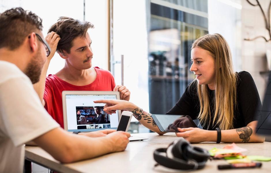 Tre personar diskuterer eit bilete på ein PC-skjerm. Foto.