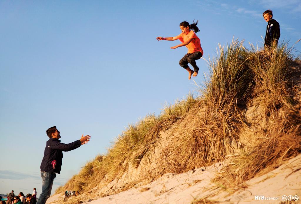 Jente som hopper fra en kant og en mann tar imot.Foto.