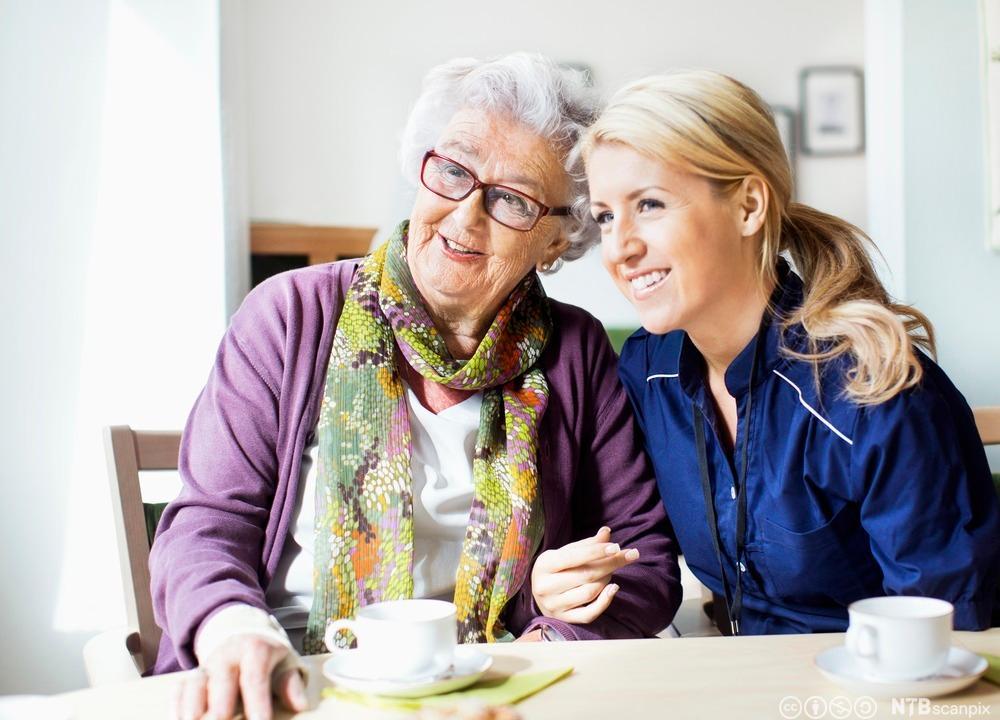 En gammel dame og en pleier drikker kaffe på en institusjon. Foto.