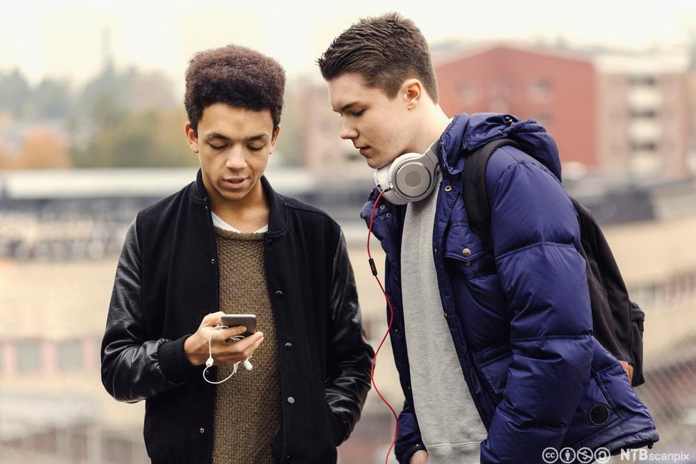 To gutter ser på en mobiltelefon. Fotografi.
