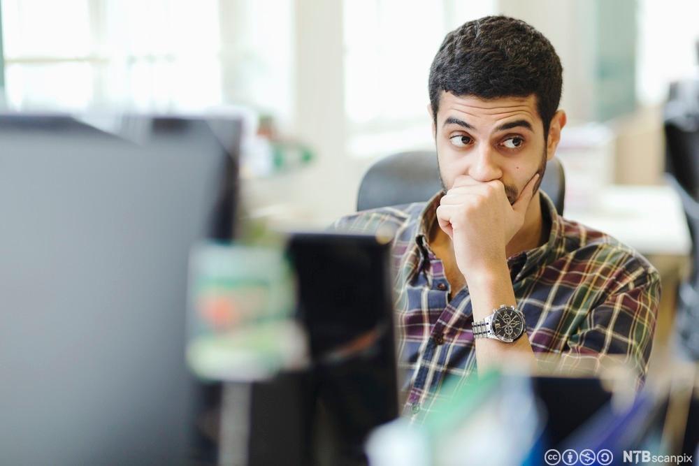 En ettertenksom mann foran PCen. Fotografi.