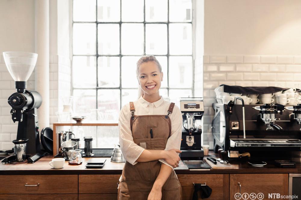 En kvinnelig barista står foran noen kaffemaskiner. Foto.