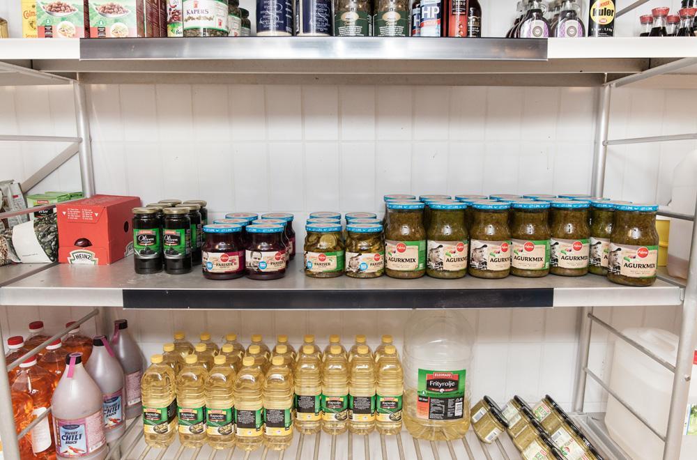 Matvarer stabler på hyller på tørrlager. Fotografi.