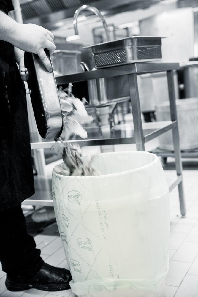 Kokk kaster matavfall i avfallsbøtte. Fotografi.
