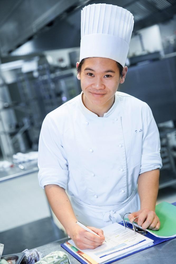 En kokk fyller ut et temperaturkontrollskjema. Foto.