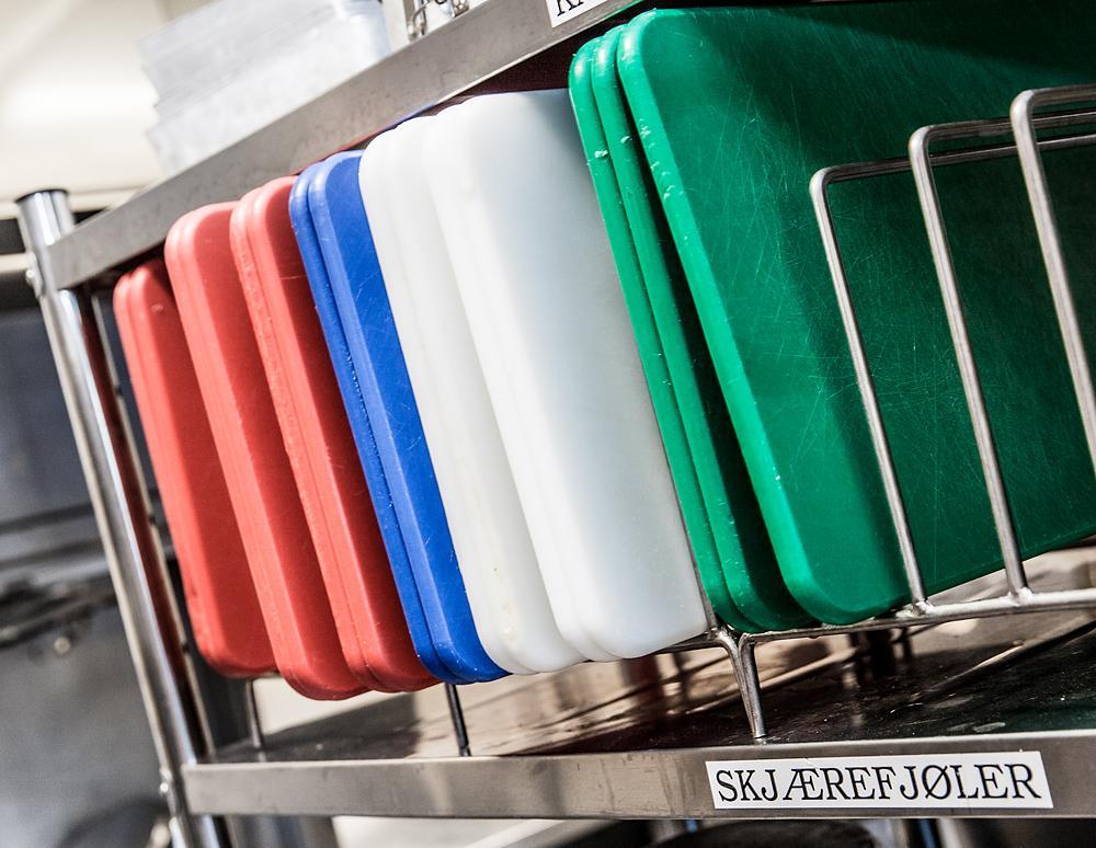 Skjærefjøler med fargekoder plassert på hylle. Foto.