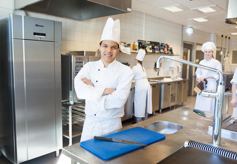 Kokk ved arbeidsstasjon. Foto.