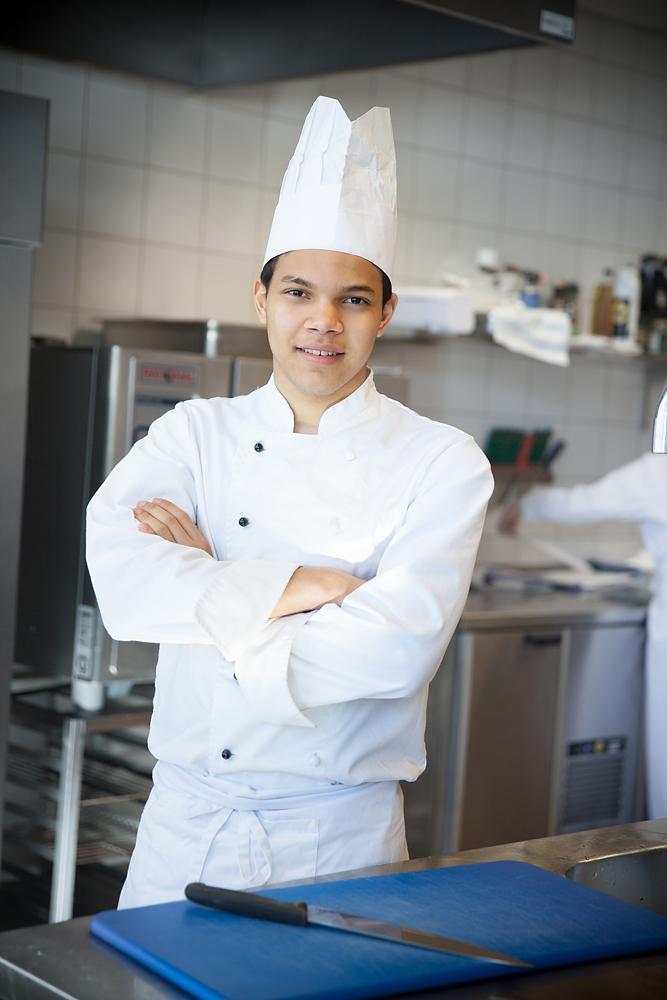 Kokk ved klargjort arbeidsstasjon. Foto.