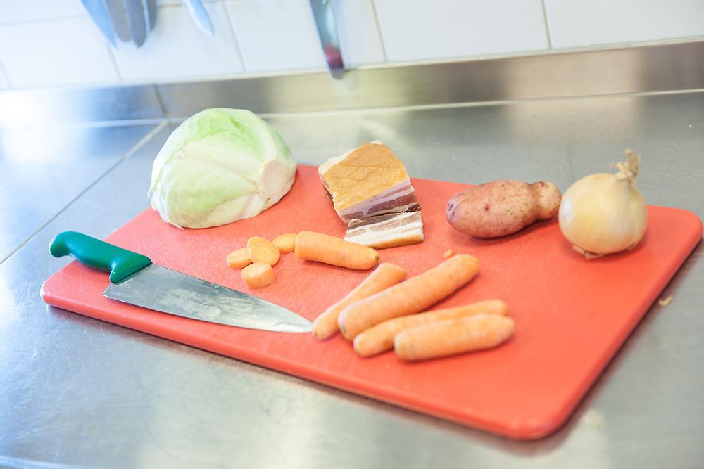 Kokkekniv, rå grønnsaker og bacon på ei skjærefjøl. Foto.