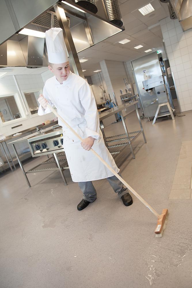 Kokk vasker gulvet på kjøkkenet. Foto.