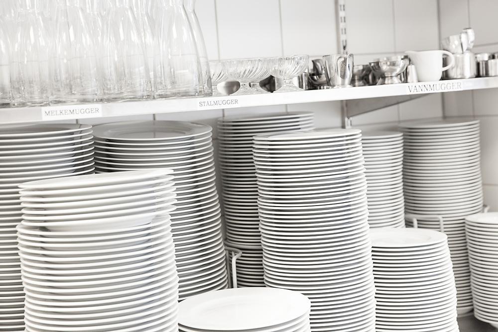 Servise og glass stablet i hyller. Foto.
