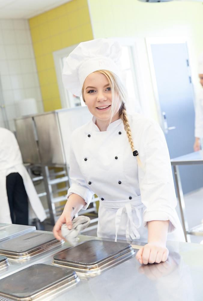 Kokk vasker kokeplatene på en ovn. Foto.
