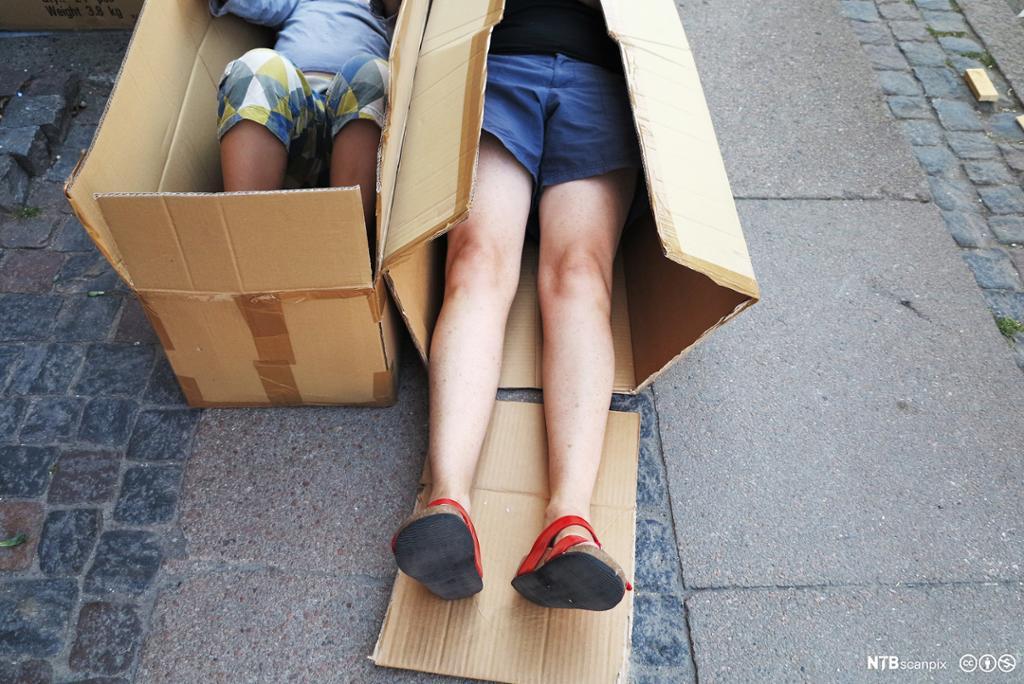 To barn ligger i hver sin pappeske. Foto