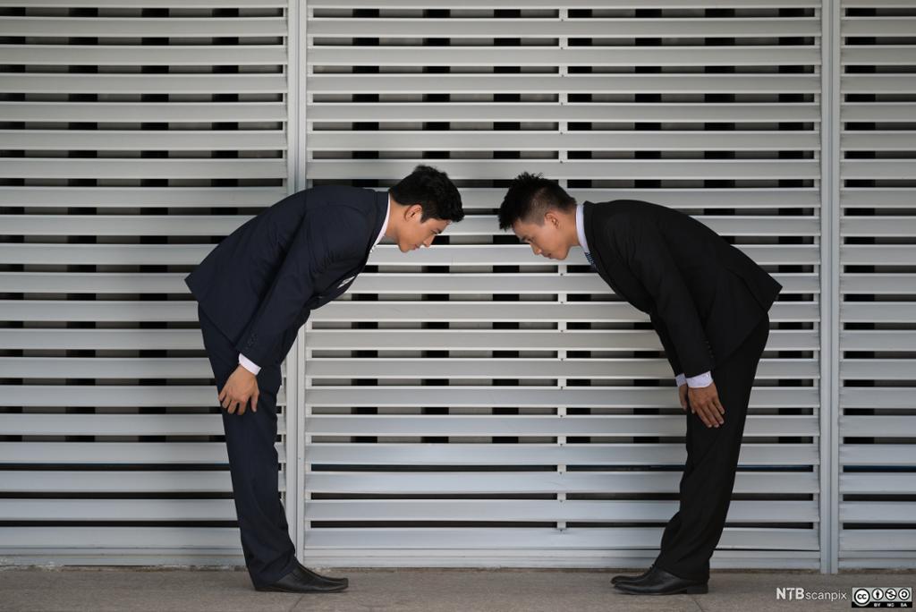 To japanske forretningsmenn bukker dypt når de hilser på hverandre. Foto.