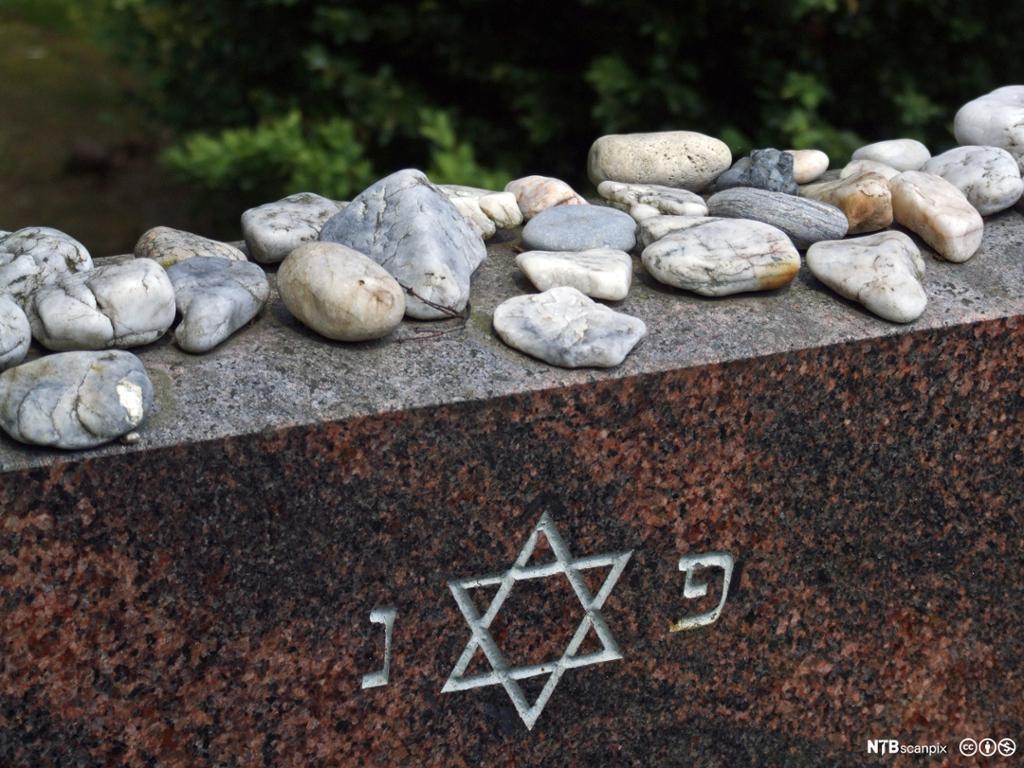 Jødisk gravstein med Davidstjerne. På gravsteinen ligger det små steiner.
