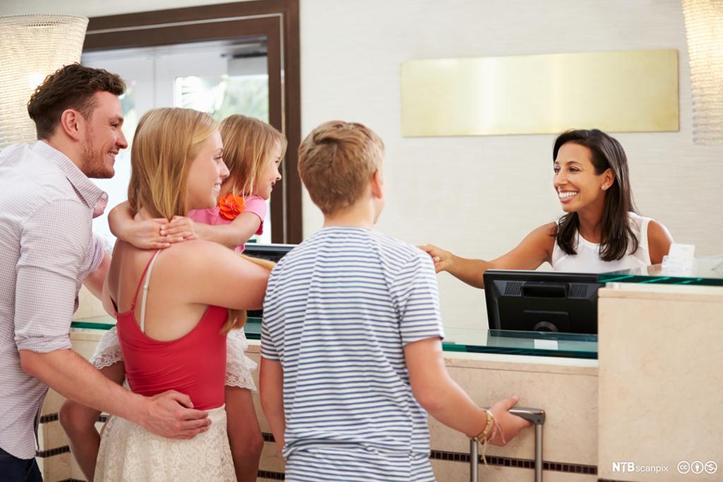 Familie sjekker inn på hotel. Foto.