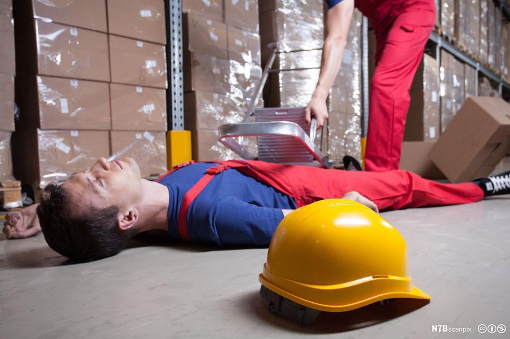 En lagerarbeider har falt ned en stige og ligger på gulvet. Foto.