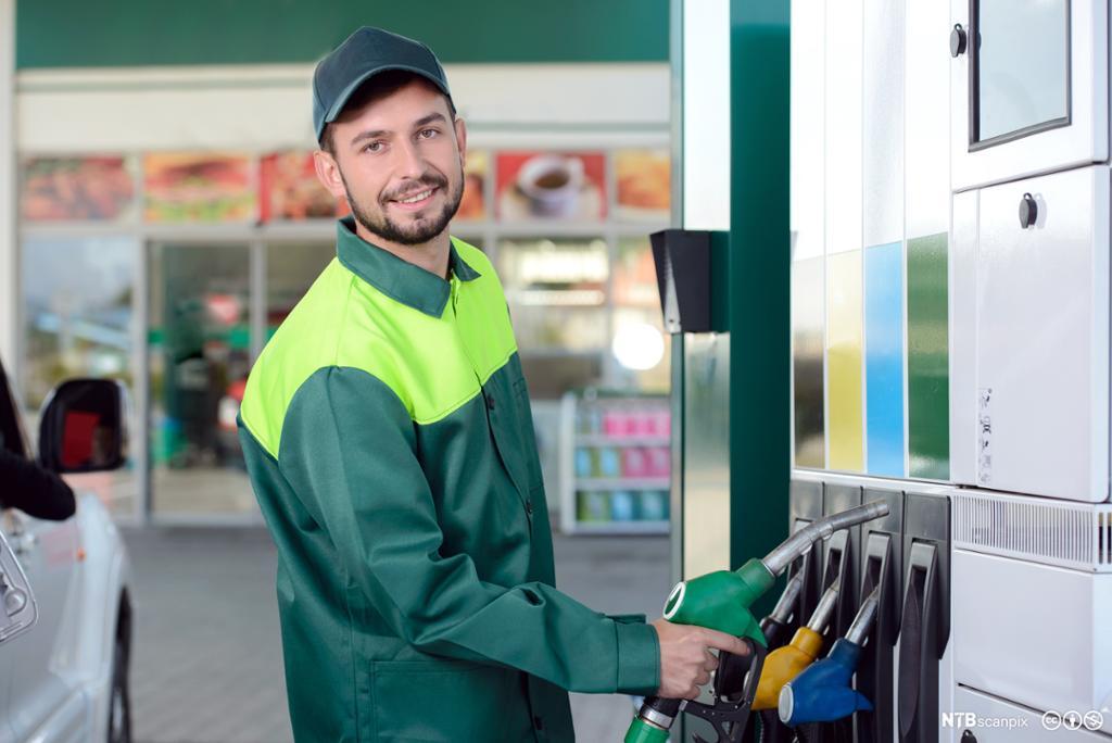 Smilende ung mann i grønne arbeidsklær og kaps står ved pumpen på en bensinstasjon. Foto.