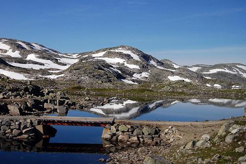 Norsk fjellandskap med bru over eit lite tjern. Foto.