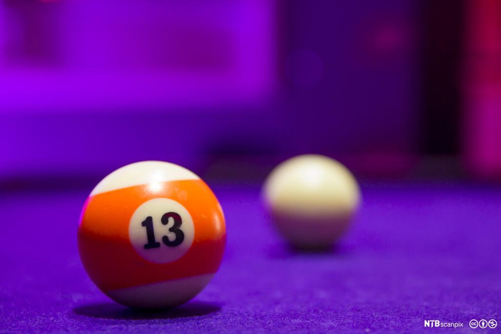 Billiardkuler på et bord. Orange kule nummer 13 i forgrunnen. Hvit kule i bakgrunnen. Foto.