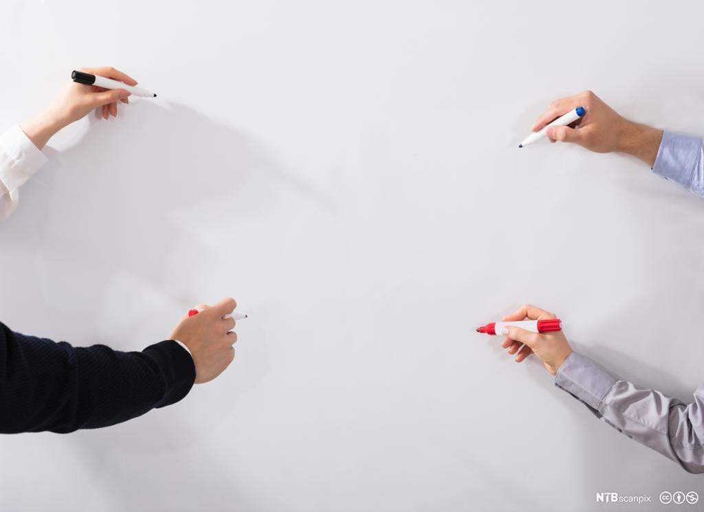 Hender som skriver på whiteboardtavle.Foto