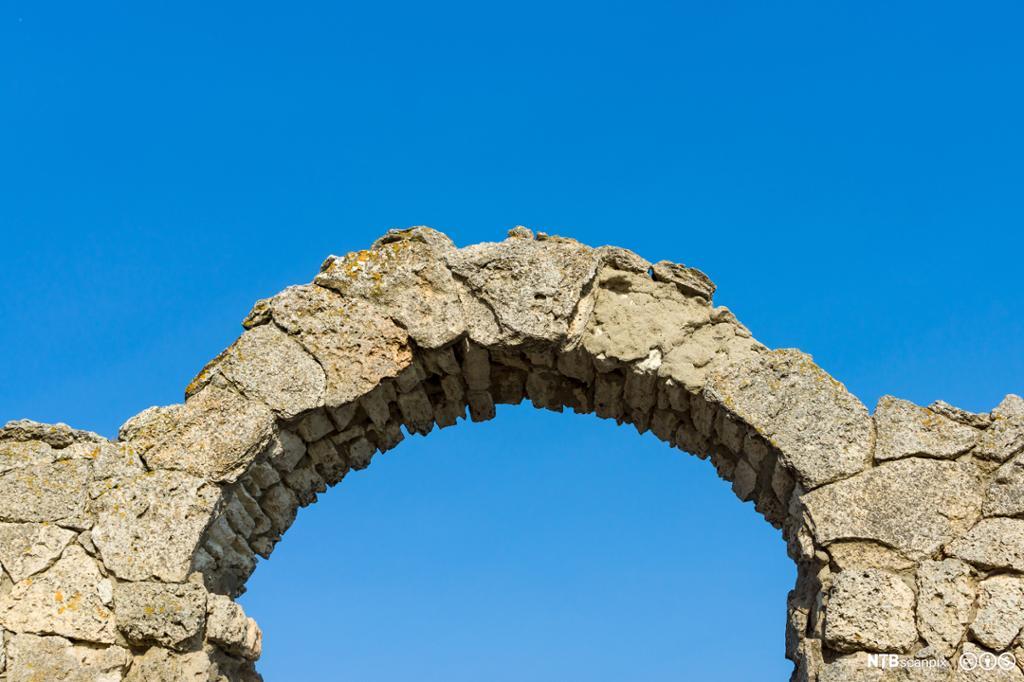 En bue av stein mot blå himmel. Deler av en ruin. Foto.