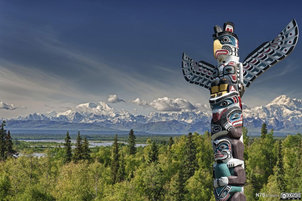 En påle med utskjærte figurer. I bakgrunnen et landskap med skog og fjell. Foto.