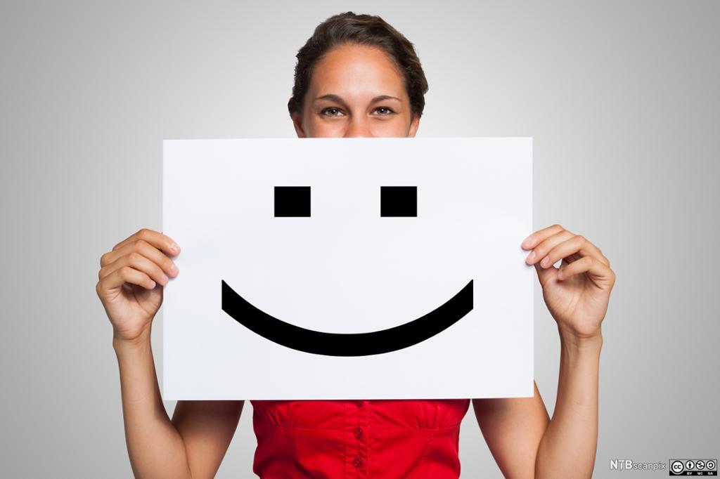 Bilde av ung kvinne som holder en plakat med et smilefjes. Foto.