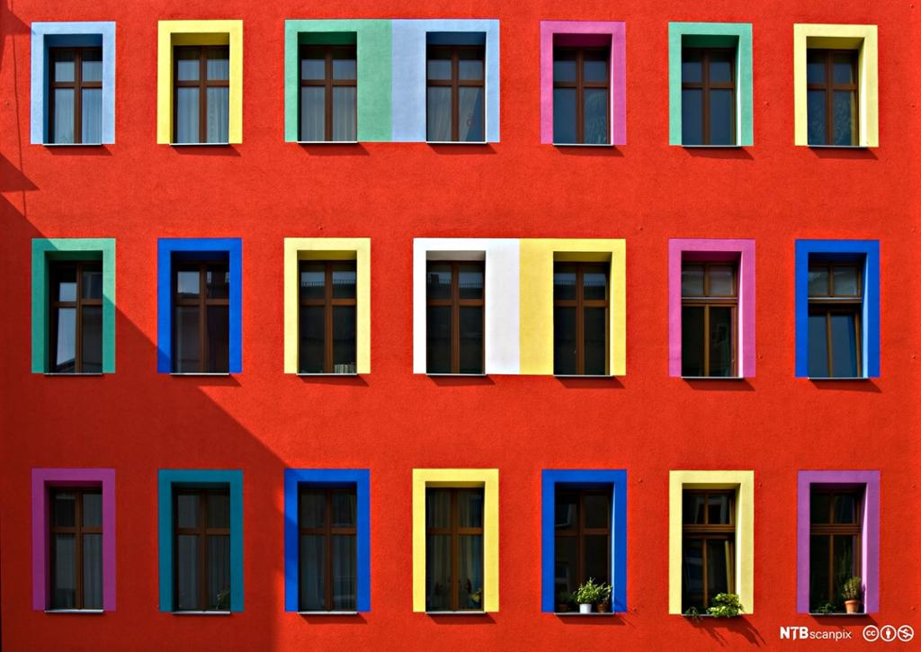 Bygård med mange fargerike vinduskarmer. Foto.
