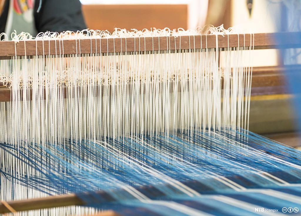Bilde av vev med hvite og blå tråder. Foto.