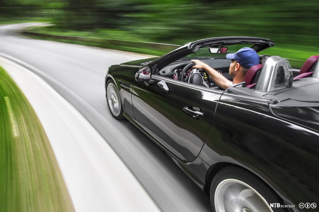 Mann i sort sportsbil kjører fort. Foto.