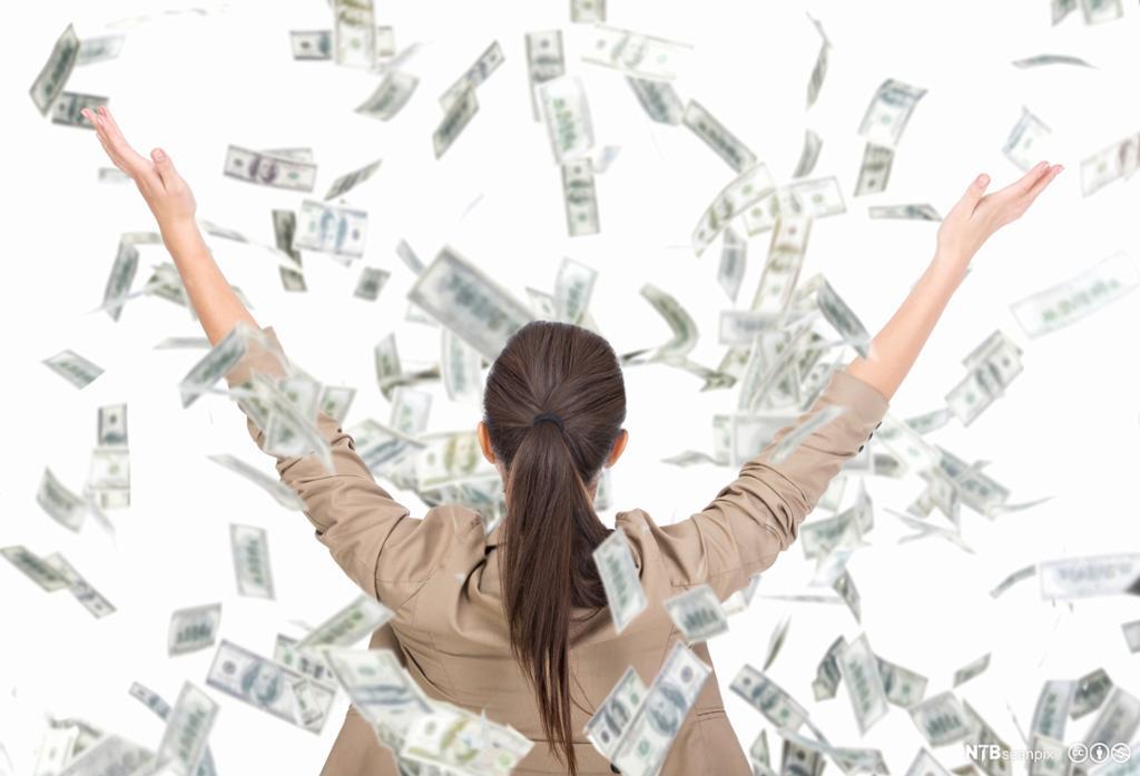 Kvinne som kaster mange pengesedler opp i lufta. Foto.
