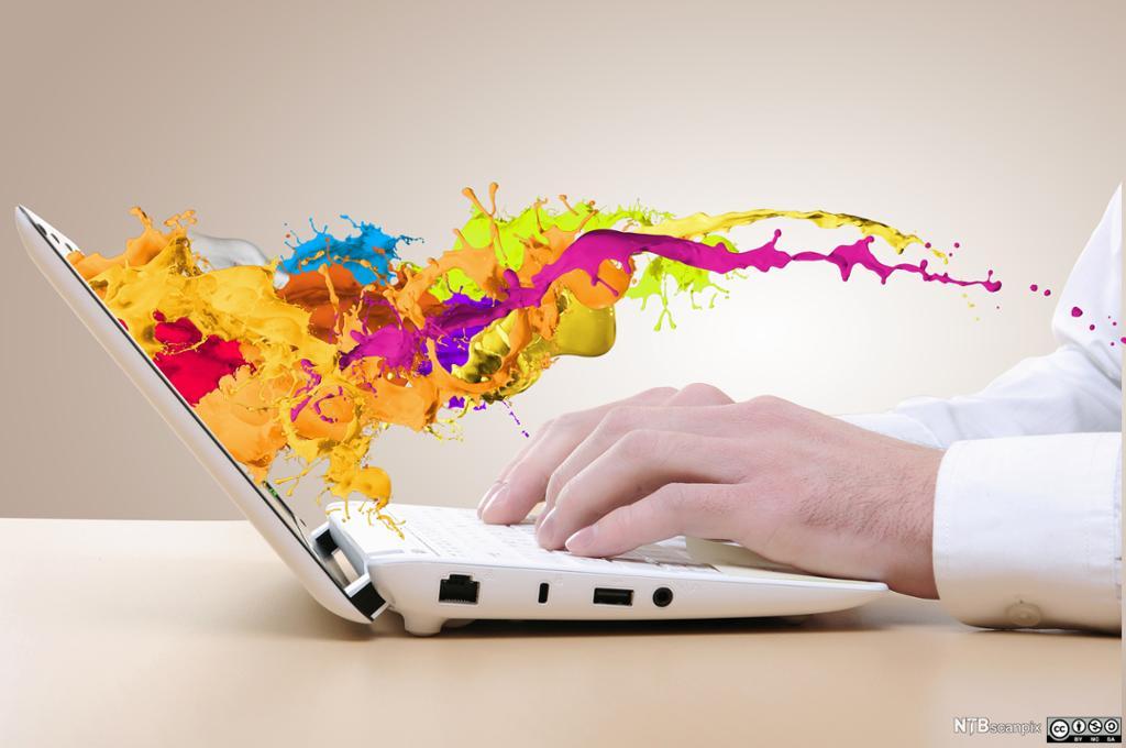 Farger spruter ut fra en laptopskjerm. Fotoillustrasjon.