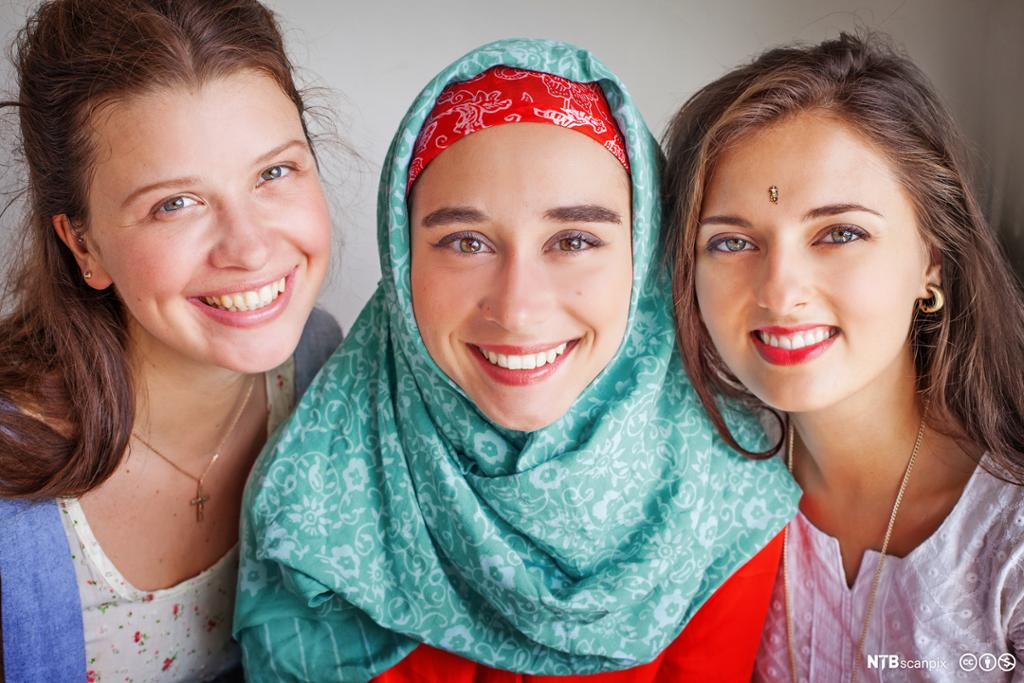 Tre unge jenter, en med kors, en med hidjab og en med bindi. Foto.