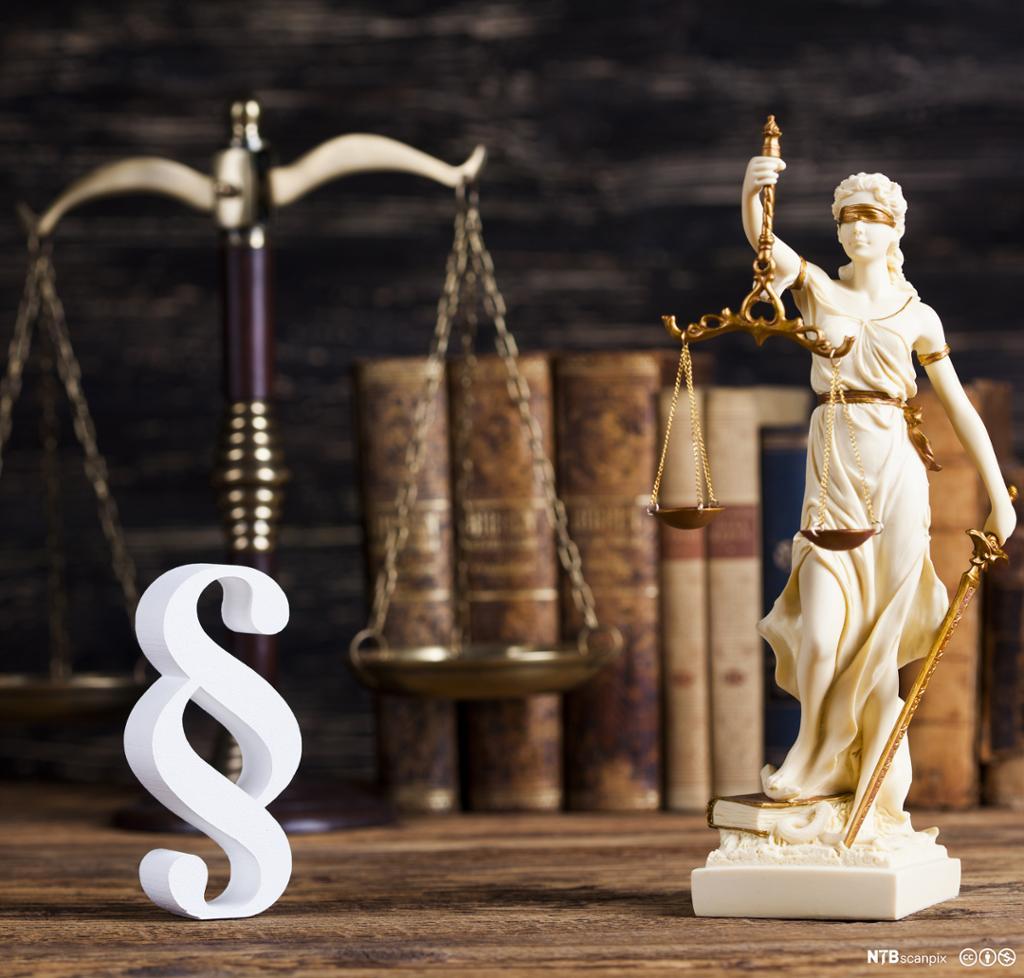 """""""Lady justice"""" som holder en vekt, paragraf i forgrunn. Foto."""