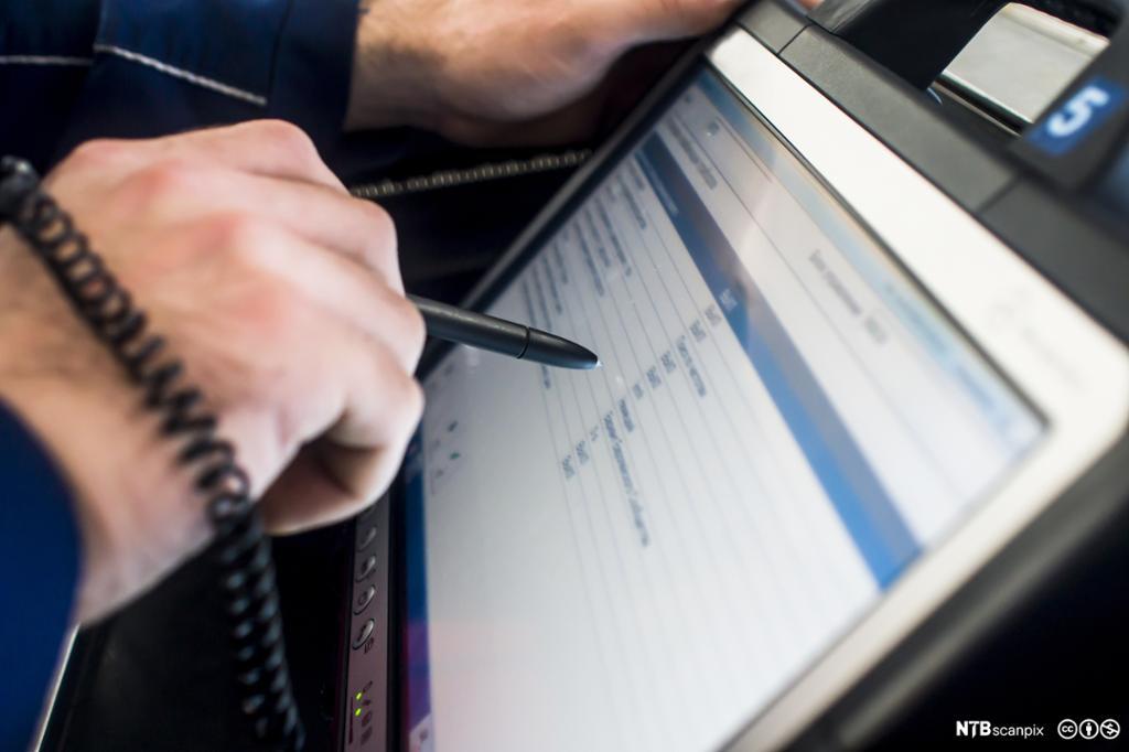 Moderne bilmekaniker bruker tablet for å finne informasjon. Foto.