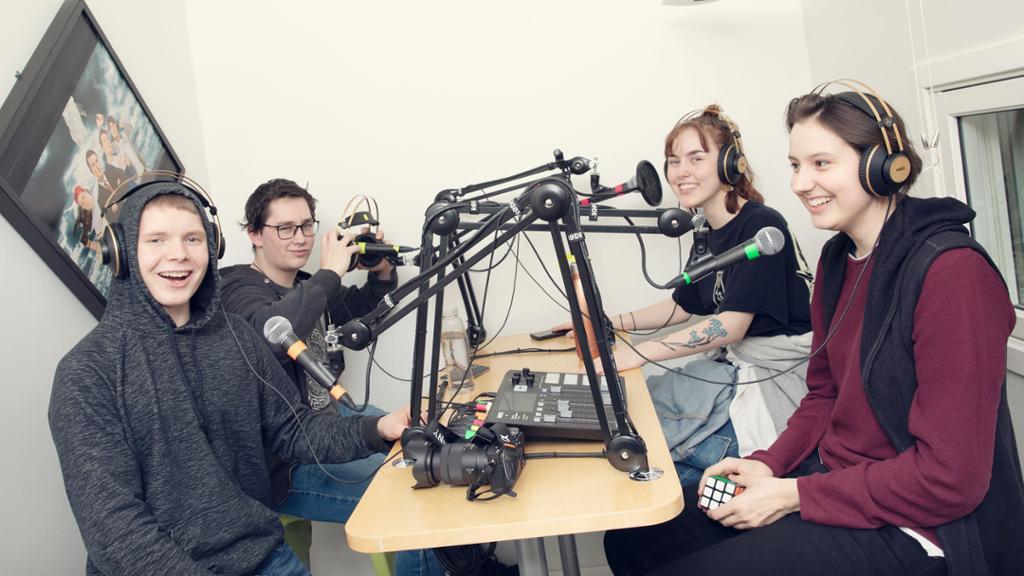 Fire elever, to gutter og to jenter, sitter overfor hverandre i et lydstudio. De har hodetelefoner på og hver sin mikrofon foran seg. Foto.