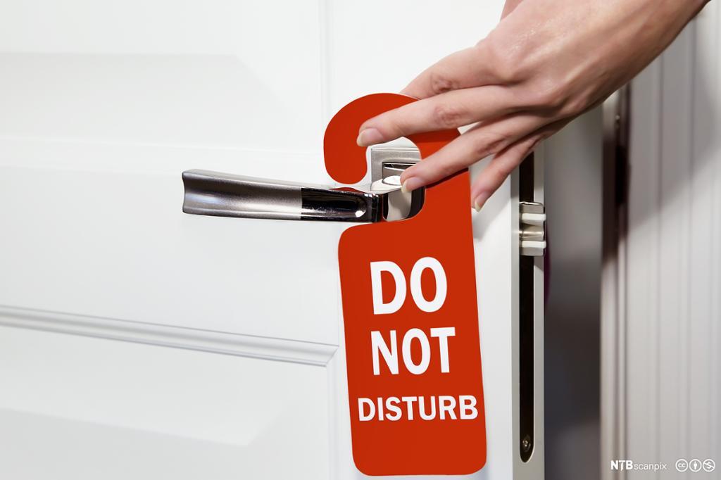 Skiltet forstyrr ikke henger på hotelldør. Foto.