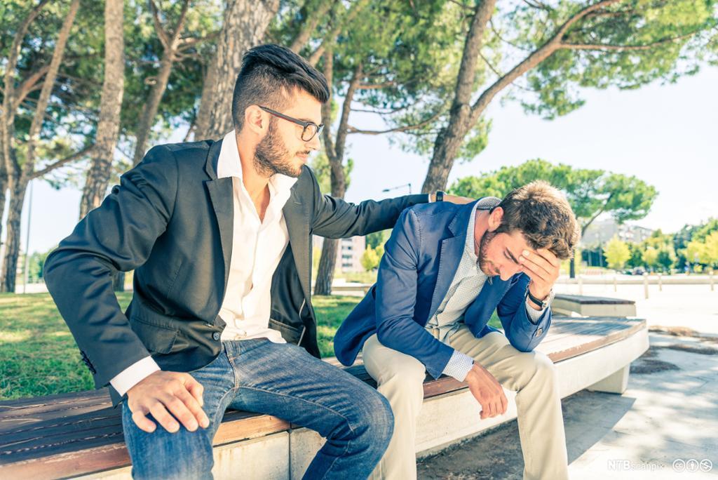 En mann sitter på en benk og trøster en annen mann. Foto.