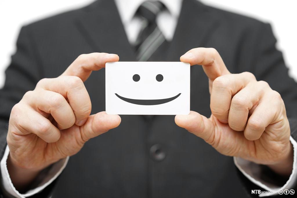 Mann som holder et kort med en smilemunn