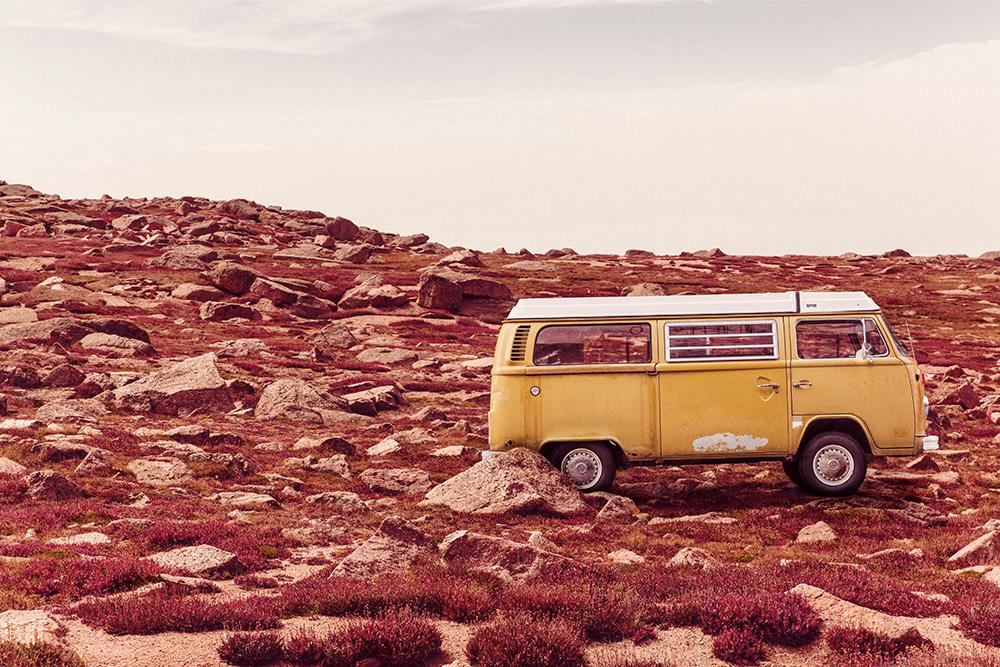 Gammel gul bil i brunsvidd landskap. Fotografi