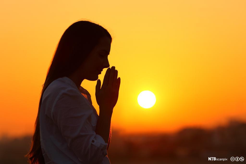 Kvinne ber i solnedgang. Foto.