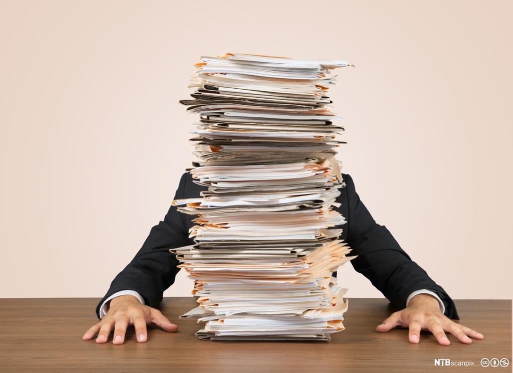 Person sitter bak en stor bunke med papir. Foto.