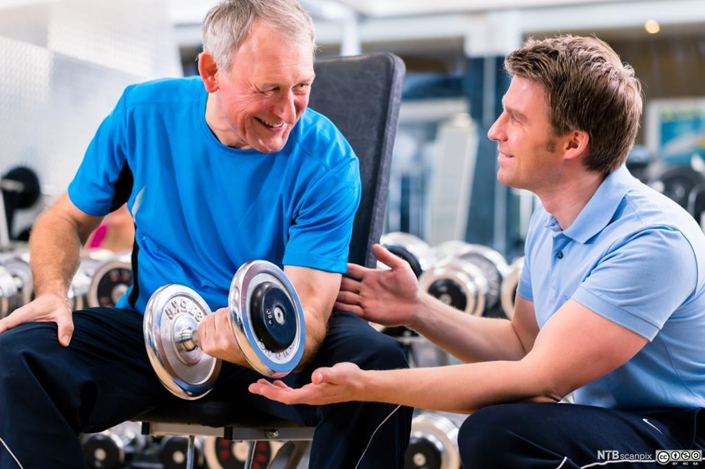 En personlig trener ved et helsestudio veileder en eldre mann som løfter vekter. Foto.