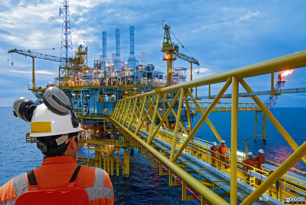 Offshorearbeider med HMS-utstyr ser på en oljeplattform. Foto.