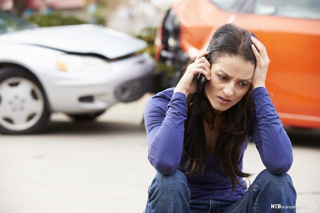 Fortvilt kvinne snakker i mobil med en bilkollisjon i bakgrunnen. Foto.
