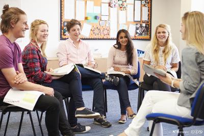Seks ungdommer som sitter i ring i et klasserom og diskuterer fag. De smiler og ser på hverandre. Foto.