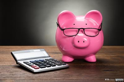 En rosa sparegris med briller står ved siden av en kalkulator. Foto.