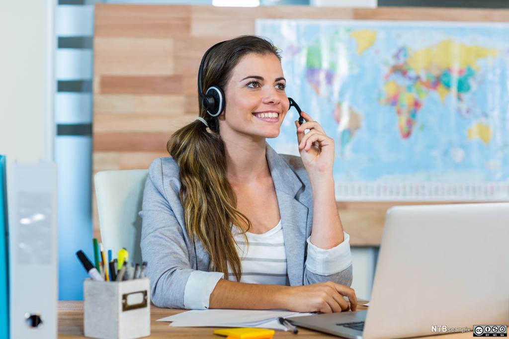 Ung kvinnelig salgskonsulent snakker i headset i et reisebyrå. Foto.