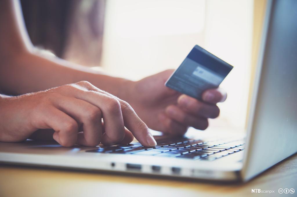 Hand som holder et kredittkort og bruker en pc